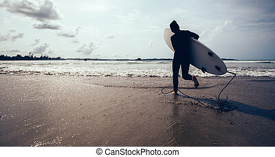 woman surfer with surfboard running on beach