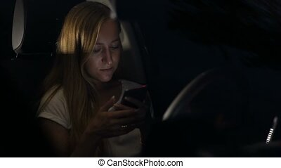 Woman surfing the net on phone in car at night