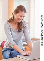 Woman surfing the web in the kitchen