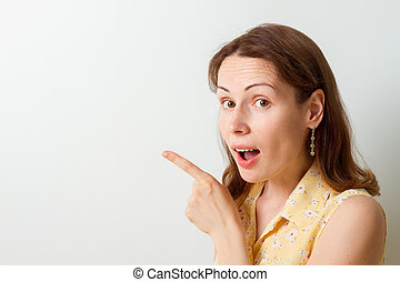 Woman surprise showing product . Presenting your product. Expressive facial expressions
