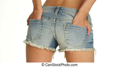 Woman swaying her hips with her hands in back pockets