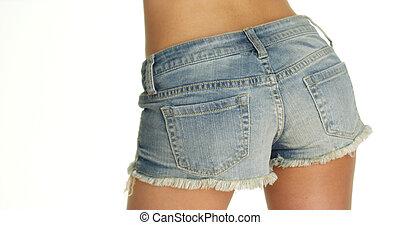 woman swaying hips in denim shorts