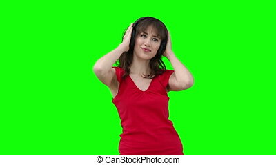 Woman swaying while holding headphones against her head
