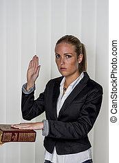 woman swears on the bible - a woman testifies as a witness...