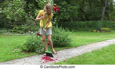 woman sweep with broom fallen rose petals on garden path. 4K