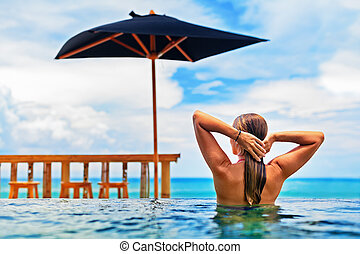 Woman swim in beach infinity pool with sea view