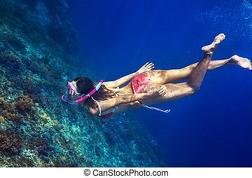 Woman swim underwater in tropical sea