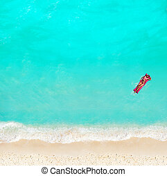 Woman swim with matrass in the water on beach