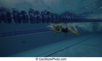 Woman swimmer in black swimsuit floating breaststroke under...