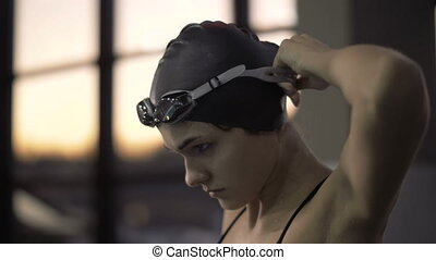 Woman swimmer putting on head glasses for swimming in...