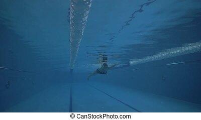 Woman swimmer swimming breaststroke in waterpool underwater...
