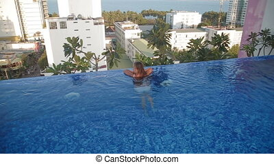 woman swimming in a roof top luxury swimming pool.