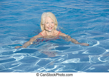 Woman swimming in outdoor pool smiling