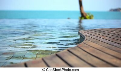 Woman swimming in pool and ocean on the background. - *oman...