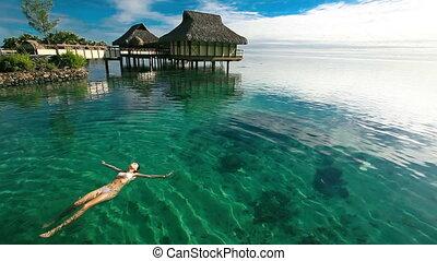 woman swimming in tropical lagoon