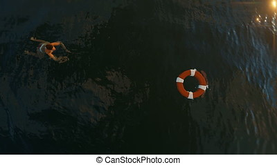 Woman Swimming towards a Lifebuoy with Sharks underneath,...