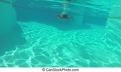 Woman swimming underwater - Young woman in bikini diving and...