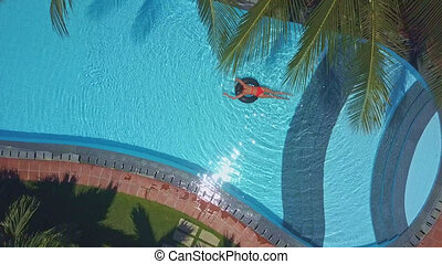 woman swims on ring in pool under palms