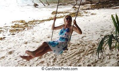 woman swinging at La Digue