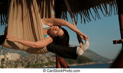Woman swinging in the hammock on the beach during the exercise of yoga