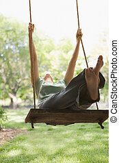 Woman Swinging on Swing - A young woman is swinging on a...