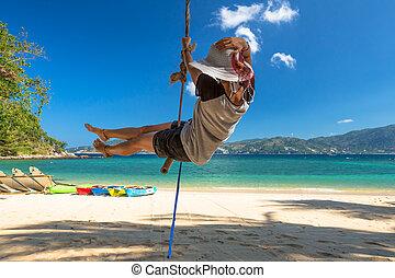 Woman swinging on the beach