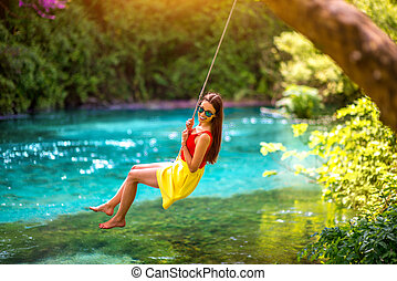 Woman swinging on the river - Happy young woman swinging...