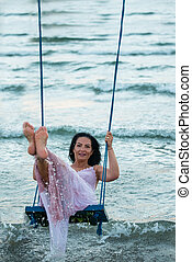 Woman swings over sea in the morning