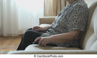 Woman switches channels of TV using remote control