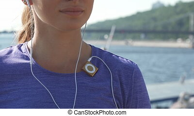 Woman switches on her mp3 player and enjoys music - Macro...