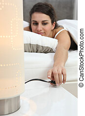 Woman switching off lamp