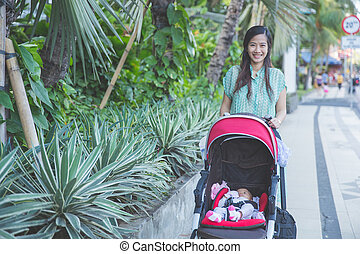 woman take a walk with her baby inside the baby stroller