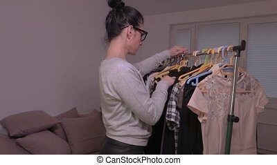 Woman take dress from the rack