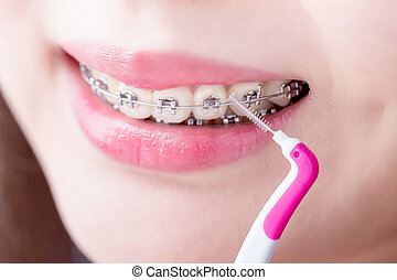 woman take interdental brush - close up of woman wear brace...