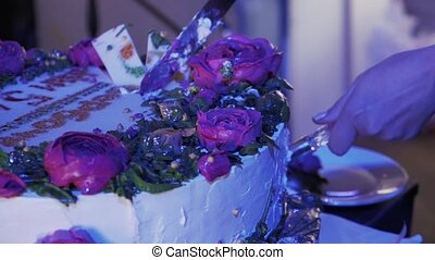 Woman take piece of huge cake with roses by knife at celebration event.
