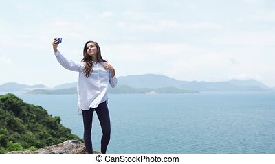 Woman take selfie photo on top of a mountain. Majestic sea shore landscape.
