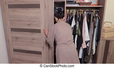 Woman take towel in wardrobe and walk away