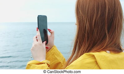Woman takes a beautiful seascape on a phone camera.