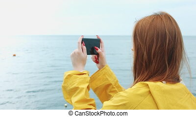 Woman takes a beautiful seascape on a phone camera. - Mid...