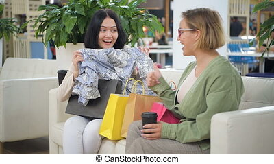 Woman takes a blouse out of shopping bag shows her friend, two women are smiling, friends are enjoying to buy a clothes, sitting on a sofa at the boutique, happy clients are talking friendly