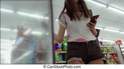 Woman takes a bottle of water from the refrigerator to the...