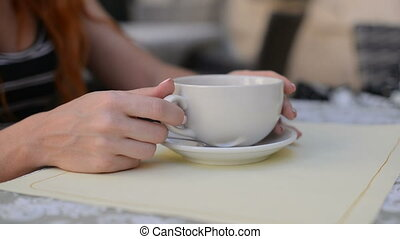 Woman takes a cup of coffee from the table