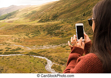 Woman takes a photo with smartphone of a landscape in Switzerland