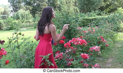 Woman takes care of flowers. - Young woman takes care of the...
