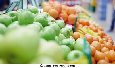 woman takes fruit in a supermarket - woman chooses fruit in...