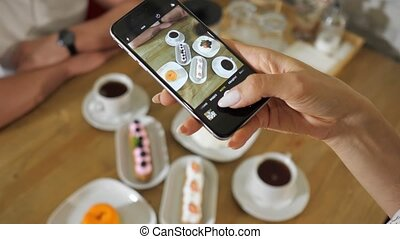young woman takes picture of different tasty cakes and tea cups with modern smartphone at wooden table closeup