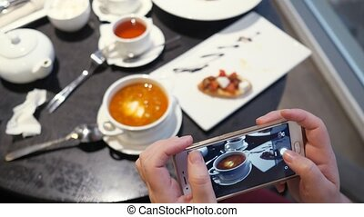 Woman takes pictures of food on the phone in a cafe