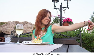 woman takes pictures of herself on her smartphone in the restaurant