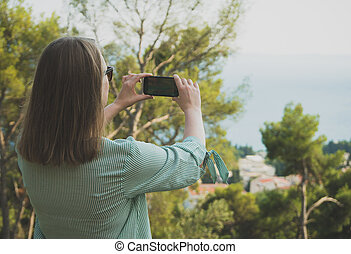 Woman takes pictures of nature by mobile phone.