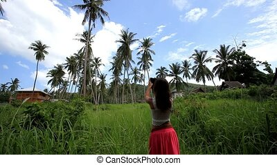 Woman takes pictures of palm trees in the jungle on Koh Samui. Thailand. HD. 1920x1080